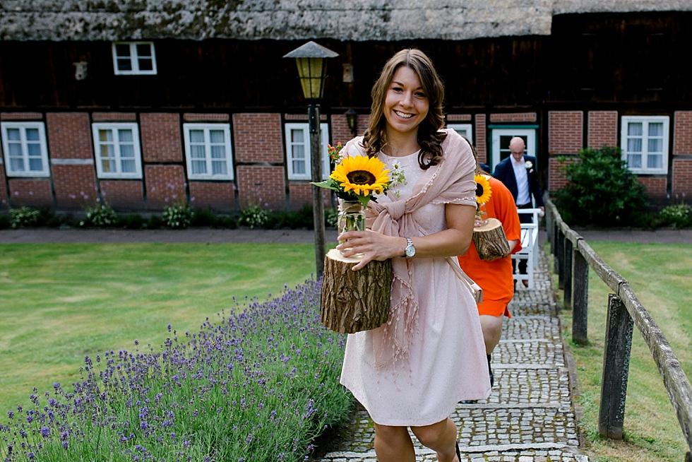 bezauberndes Lächeln, Frau mit Sonnenblume in der Hand, Heiraten im Haverbeckhof Bispingen - Jana Richter fotografie-44.jpg
